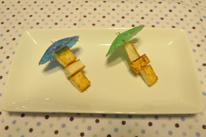 Pan fried tofu served on umbrella toothpicks